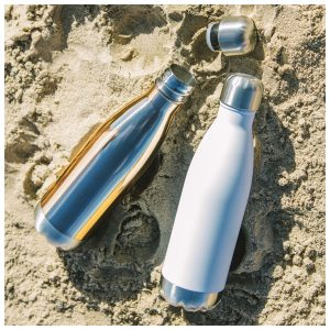 Two stainless steep water bottles, one white and one chrome, lying in the sand