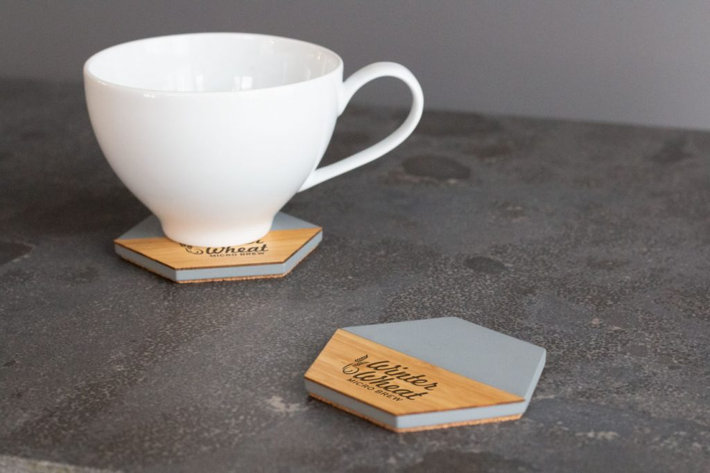 A picture of two branded concrete coasters on a table with a mug