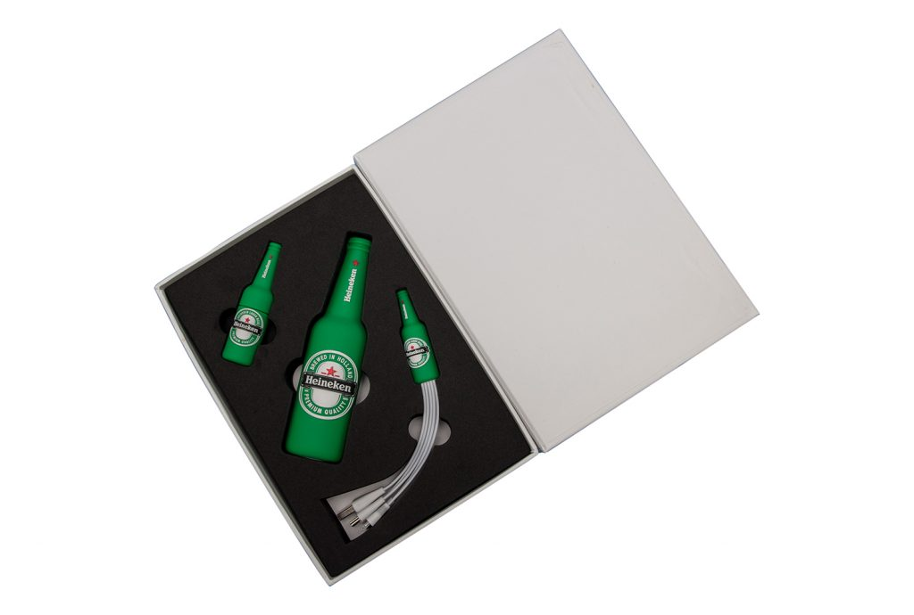 A picture of a set comprised of a power bank, a USB drive, and a cord adaptor, all of which are shaped like bottles of Heineken beer